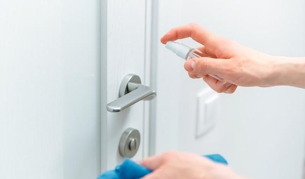 Avvicinamento. uomo pulito che spruzza spray antisettico sulla maniglia della porta.