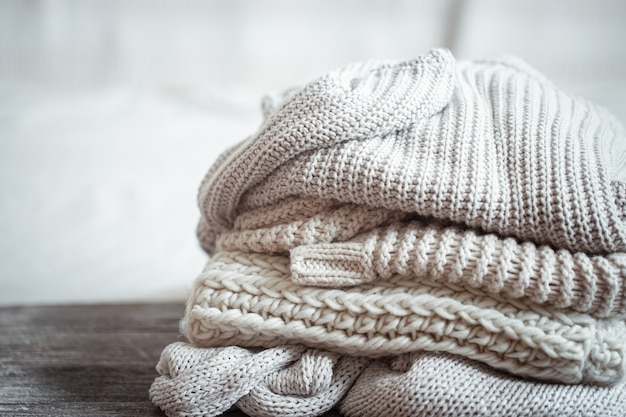 Primo piano di articoli lavorati a maglia ordinatamente piegati di colore pastello su sfondo chiaro.