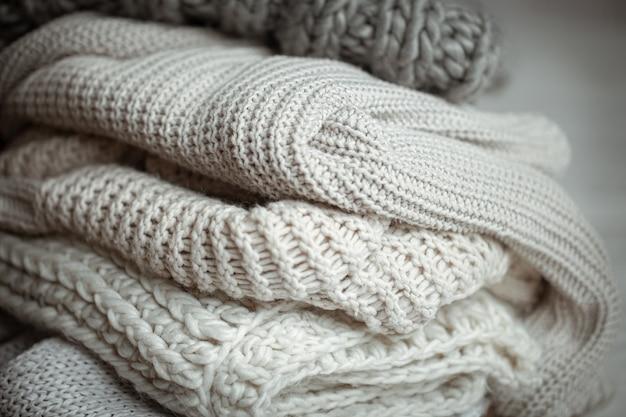 Primo piano di articoli lavorati a maglia ordinatamente piegati di colore pastello.