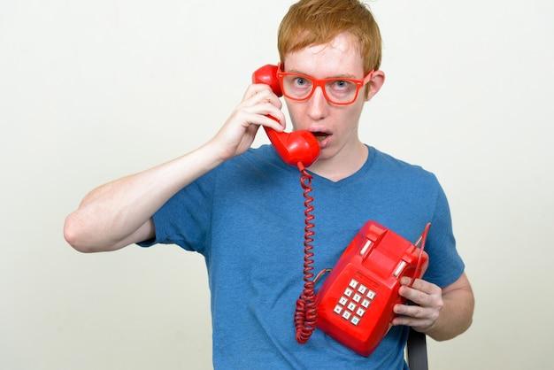 Primo piano di uomo nerd con i capelli rossi che indossa occhiali isolati