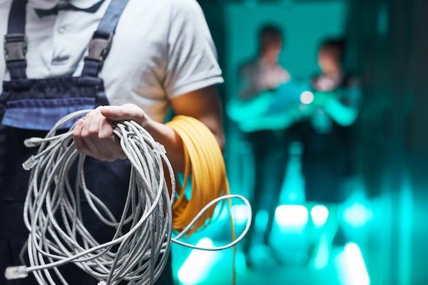 Primo piano dell'ingegnere di rete che tiene i cavi nella sala server durante i lavori di manutenzione nel data center, spazio di copia