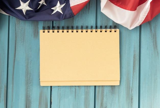 Chiusura del blocco note su sfondo di legno, bandiere usa, americano.