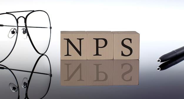 Close-up di nps blocchi di legno su sfondo nero con occhiali e penna
