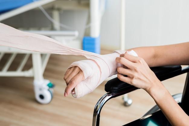 Close-up di un'infermiera bendaggi con stecca il braccio della mano del paziente femminile a causa del braccio rotto per una migliore guarigione sedersi su una sedia a rotelle nell'ospedale della stanza.