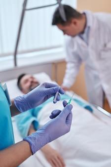 Primo piano dell'infermiera in guanti chirurgici che sta al letto del paziente e prepara l'ago della siringa per iv