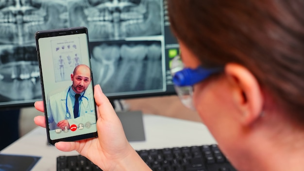 Primo piano di un'infermiera che parla in videochiamata con uno stomatologo specialista utilizzando il telefono cellulare seduto nella moderna clinica odontoiatrica davanti al pc con radiografia digitale. medico di odontoiatria che spiega i sintomi del paziente