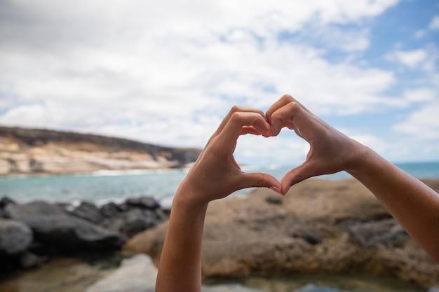 Primo piano sulle mani a forma di cuore di una ragazza che si diverte e si gode l'estate in spiaggia ama il concetto di natura