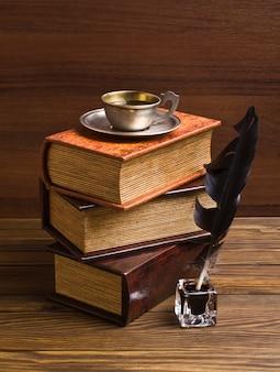 Primo piano su vecchi libri, piuma e calamaio sul tavolo di legno