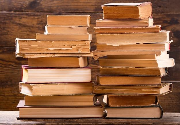 Primo piano di vecchi libri su uno scaffale di legno