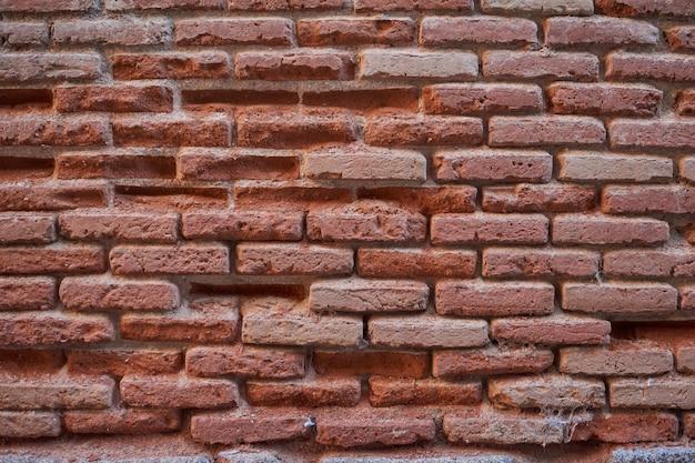 Chiuda in su di vecchio muro di mattoni rotto per priorità bassa e struttura