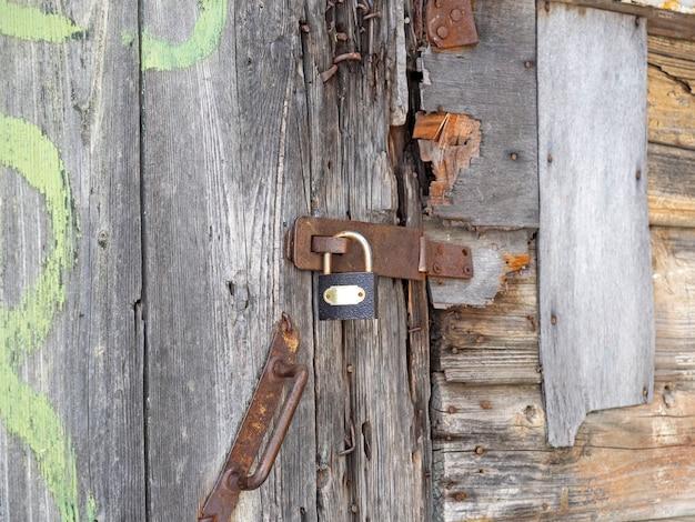 Primo piano di una vecchia porta di legno fatiscente chiusa con un lucchetto