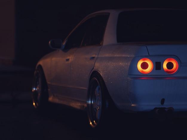 Primo piano di una vecchia auto sportiva alla deriva nella notte parcheggio. luci rosse posteriori