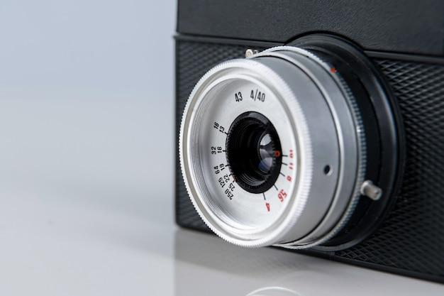 Chiuda in su della vecchia lente della fotocamera a pellicola telemetro sulla superficie bianca.
