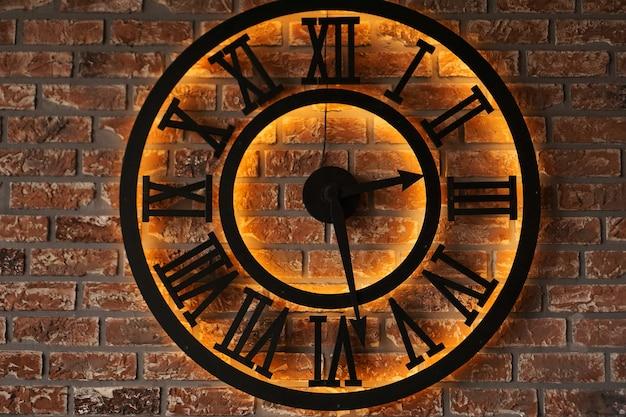Primo piano vecchio orologio da parete in metallo stile retrò vintage su sfondo di muro di mattoni grunge - stile loft