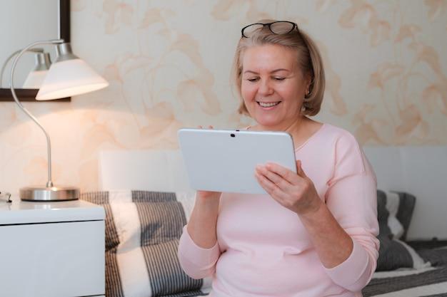 Close-up più anziana bella bionda donna senior 50-60 anni seduto divano con tablet notebook elettronico. tecnologie moderne per la vecchia generazione.