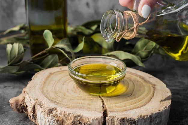 Olio d'oliva del primo piano che versa nella ciotola