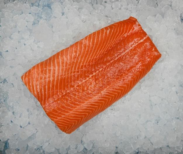 Chiudere un filetto di pesce salmone crudo fresco su ghiaccio tritato, vista dall'alto in alto, direttamente sopra