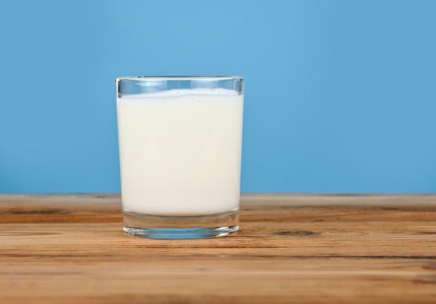 Chiudi un bicchiere pieno di latte fresco su un tavolo di legno su sfondo blu
