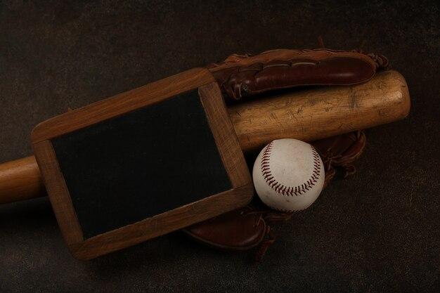Chiudere una vecchia palla da baseball, mazza di legno, guanto vintage in pelle usurata e segno di lavagna su sfondo marrone scuro grunge, vista dall'alto in elevazione, direttamente sopra