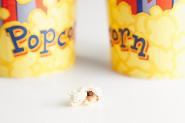 Primo piano di un pezzo di popcorn vicino a due tazze di cartone. concetto di cibo gustoso.