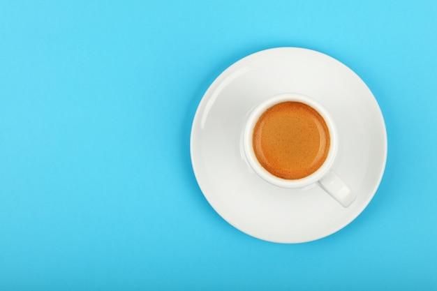 Chiudere una tazza bianca piena di caffè espresso sul piattino su sfondo blu, vista dall'alto in elevazione, direttamente sopra