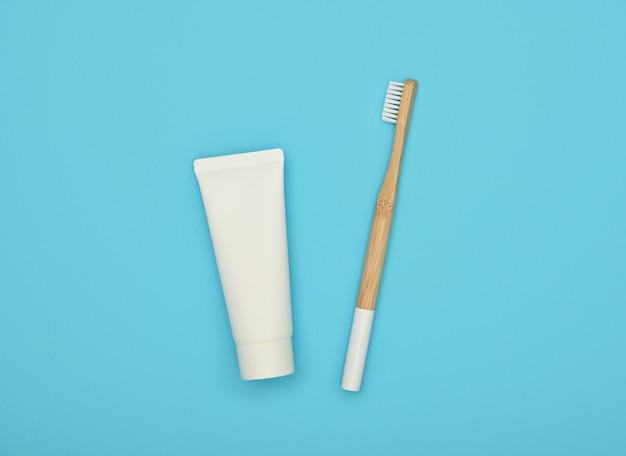 Chiudere un tubo di dentifricio bianco e spazzolino da denti di bambù in legno naturale su sfondo blu, piatto laico, vista dall'alto in alto, direttamente sopra