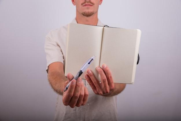 Primo piano di un'agenda vuota aperta e di una penna tenuta da un uomo sul retro sfuocato.