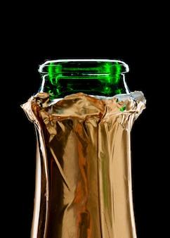Primo piano della bottiglia di champagne aperta isolata sul nero