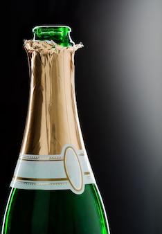 Primo piano della bottiglia di champagne aperta con etichetta