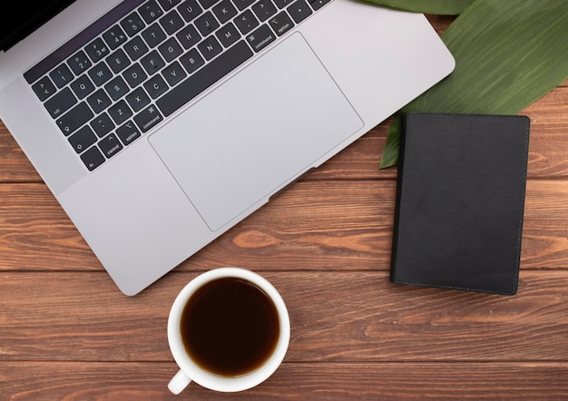 Chiudere il portatile aperto con caffè e notebook sulla vecchia scrivania in legno. stile piatto. vista dall'alto