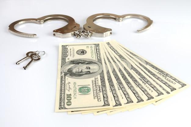 Close-up di manette in metallo aperto, chiavi e pila di dollari americani in contanti isolato su sfondo bianco. guadagni illegali, tangenti, serie di corruzione