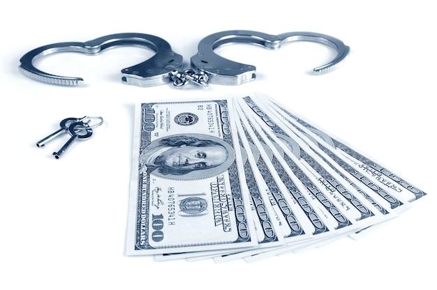 Close-up di manette in metallo aperto, chiavi e pila di dollari americani in contanti isolato su sfondo bianco
