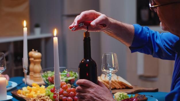 Primo piano di aprire una bottiglia di vino durante una cena romantica. coppia anziana matura seduta al tavolo in cucina, parlando, godendosi il pasto, celebrando il loro anniversario nella sala da pranzo.
