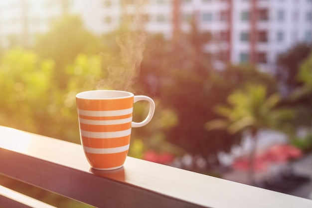 Chiuda sulla tazza di caffè arancio sul balcone dell'hotel e sulla vista vaga di costruzione