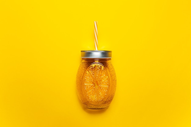 Primo piano della tazza di vetro del succo d'arancia con paglia