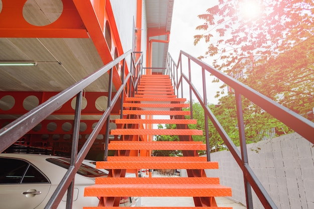 Chiuda in su della scala d'acciaio arancione o scala all'esterno dell'edificio.