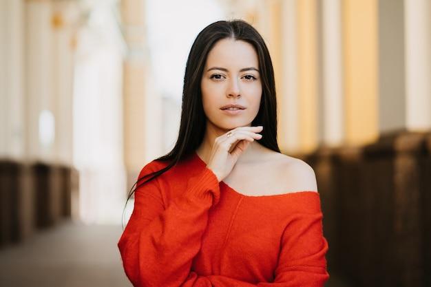 Chiuda sul ritratto all'aperto di giovane donna splendida vestita in maglione rosso