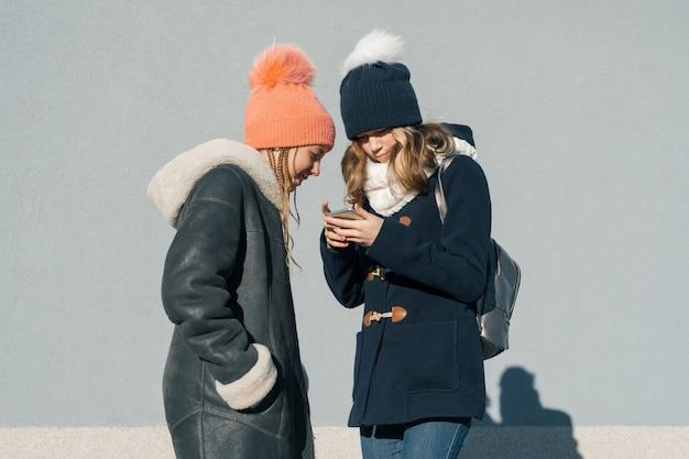 Un ritratto all'aperto di inverno del primo piano di due ragazze adolescenti