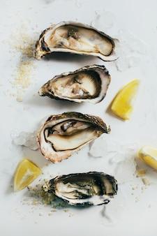Primo piano su ostriche con limone su sfondo bianco vista dall'alto
