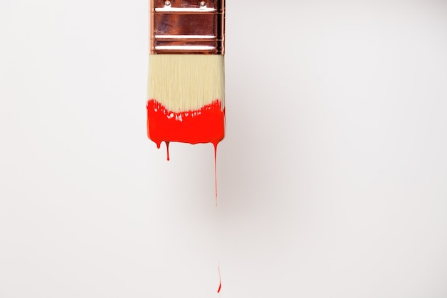 Pennello di close-up con vernice rossa liquida gocciola dal pennello, tema di disegno di design creativo, sfondo bianco, orizzontale, vista laterale, copia spazio per il testo