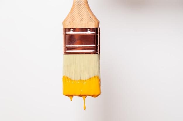 Il pennello del primo piano con vernice gialla liquida gocciola dal pennello