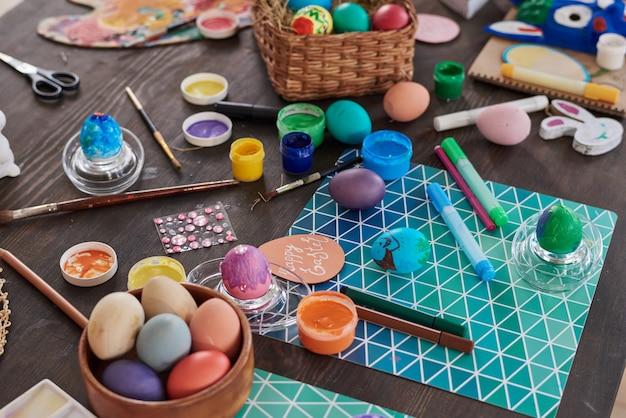 Primo piano di uova di pasqua dipinte e vernici sul tavolo che si preparano per la decorazione in vacanza