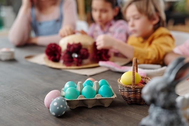 Primo piano di uova di pasqua dipinte su un tavolo di legno preparato per pasqua con la famiglia sullo sfondo