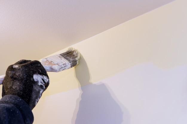 Primo piano delle mani del pittore con la pittura del bordo del muro con il pennello un appartamento