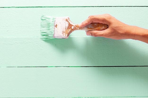 Chiuda sul colore verde della pittura della mano dell'uomo del pittore sul tavolo della plancia di legno con lo spazio della copia, interni luminosi di progettazione creativa e come dipingere la superficie di legno.