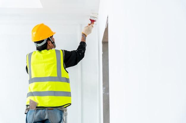 Primo piano pittore uomo che dipinge il muro in un edificio incompiuto, con pennello, isolato su grande spazio vuoto con scala in legno in cantiere