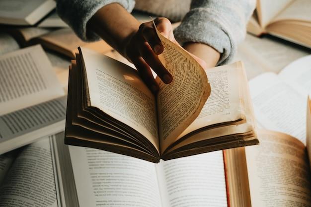Primo piano di un paio di mani nere, leggendo un vecchio libro