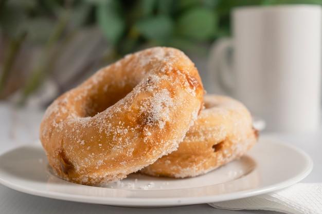 Primo piano di un paio di ciambelle zuccherate e ripiene di caramello su un piatto bianco con una tazza bianca. concetto di colazione.