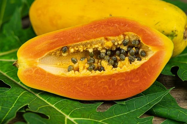 Chiuda sulla fetta di papaia con foglia di papaia sul fondo della tavola in legno.