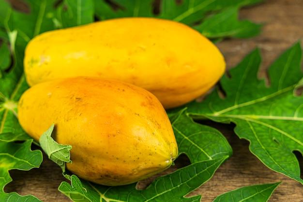 Primo piano papaia con foglia di papaia sul fondo della tavola in legno.